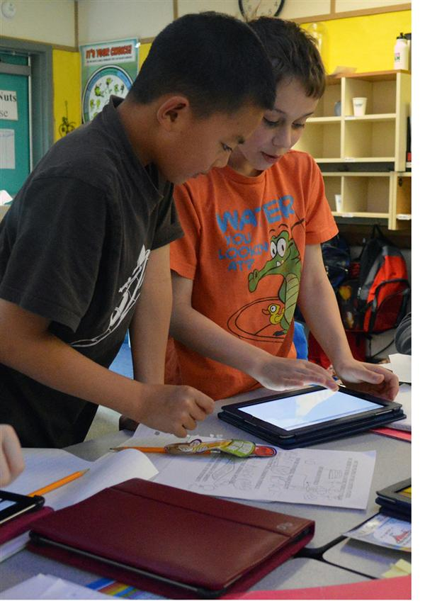 elementary students collaborate using an iPad
