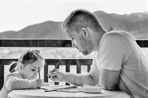 girl and father working on paper