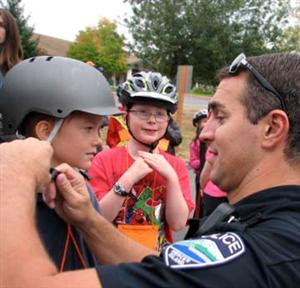 Policeman assisting boy with helmet
